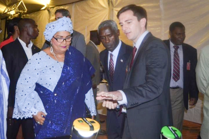 Andrew Lala (r) explains Clair de Lune's solar lights to US Ambassador Mushingi and First Lady Chantal Compaoré.